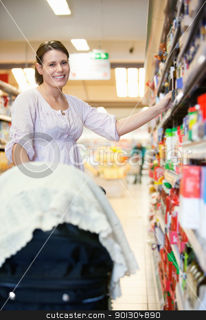 Mother in Supermarket stock photo, Smiling mother with baby stroller in shopping centre looking at camera by Tyler Olson