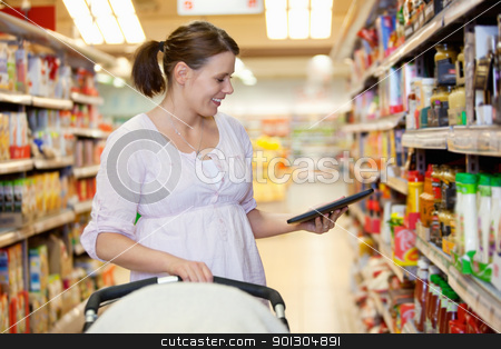 Smiling woman looking at digital tablet in shopping centre stock photo, Smiling woman looking at digital tablet in shopping centre while holding baby stroller by Tyler Olson
