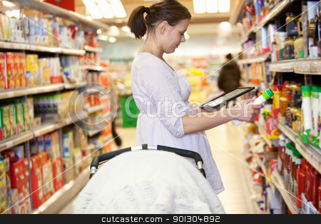 Product Comparison stock photo, Woman comparing products with a tablet comptuer in a supermarket by Tyler Olson