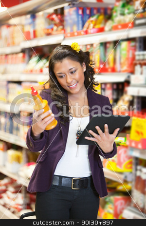 Woman looking at a product while holding digital tablet in shopp stock photo, Young smiling woman looking at a product while holding digital tablet in shopping centre by Tyler Olson