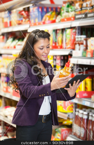 Online Product Comparison in Supermarket stock photo, A happy woman using a tablet computer in a supermarket to check out a product by Tyler Olson
