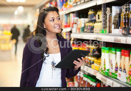 Tablet PC Shopping List stock photo, Smiling woman looking at the products while holding digital tablet with people in the background by Tyler Olson