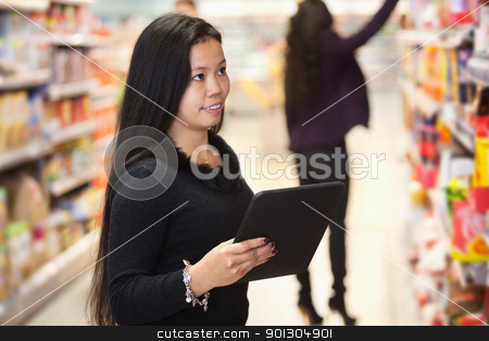 Woman using digital tablet in shopping centre stock photo, Young woman looking at the products while using digital tablet in shopping centre with person in the background by Tyler Olson