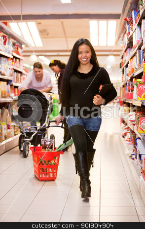 Asian Woman Grocery Store stock photo, An asian woman in a grocery store with an ipad and basket by Tyler Olson