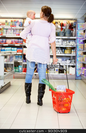 Mother with Child in Grocery Store stock photo, Rear view of woman carrying baby while pulling shopping basket in shopping centre by Tyler Olson