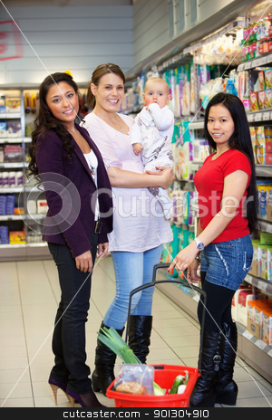 Mother with Child and Friends in Supermarket stock photo, Woman holding baby and standing with friends while looking at camera by Tyler Olson