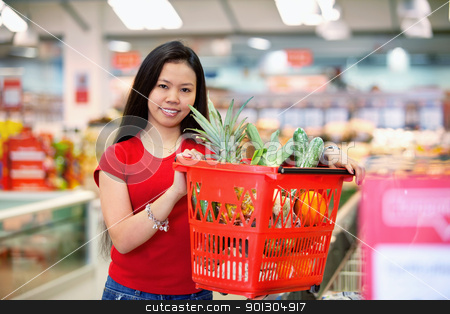 Asian Woman in Supermarket stock photo, Smiling woman holding basket filled with fruits in shopping centre and looking at camera by Tyler Olson