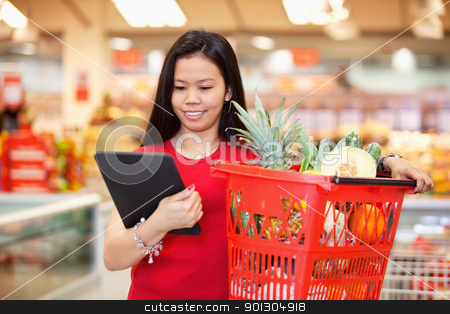 Woman looking at digital tablet stock photo, Smiling woman looking at digital tablet by Tyler Olson