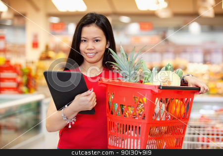Portrait of woman with digital tablet stock photo, Young woman with digital tablet holding fruit basket in shopping centre and looking at camera by Tyler Olson
