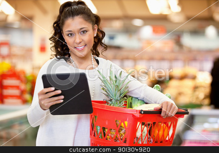 Woman with Tablet PC Shopping List stock photo, Woman with digital tablet holding fruit basket in shopping centre and looking at camera by Tyler Olson