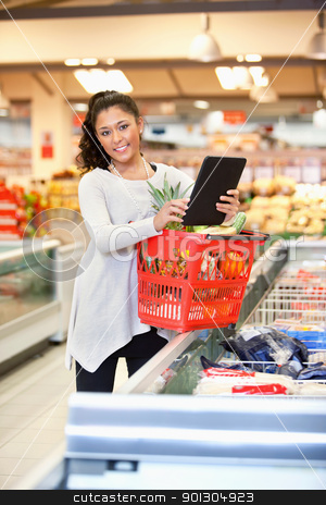 Shopper in store using digital tablet stock photo, Shopper with basket holding digital tablet and looking at camera by Tyler Olson