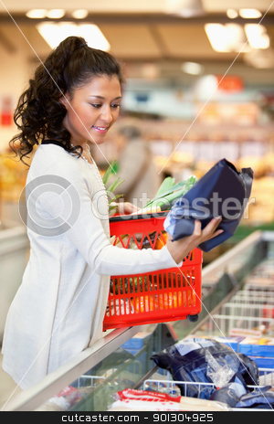 Smiling woman looking at product stock photo, Smiling young woman with red basket holding bag in shopping store by Tyler Olson