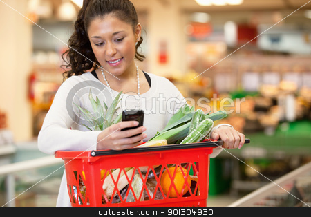 Smiling woman using mobile phone in shopping store stock photo, Smiling young woman using mobile phone while shopping in shopping store by Tyler Olson