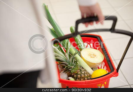 Supermarket Basket Detail stock photo, High angle view of human hand carrying red basket filled with fruits and vegetables by Tyler Olson