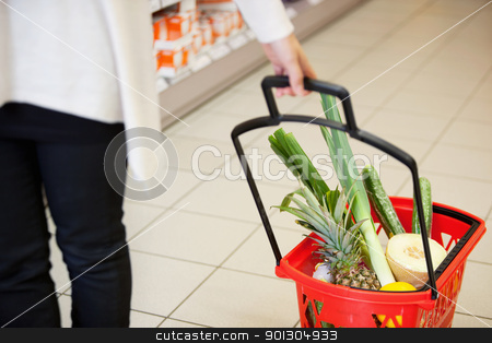 Woman pulling Shopping Basket in Grocery Store stock photo, High angle view of human hand carrying red basket filled with fruits and vegetables by Tyler Olson