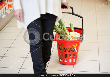 Woman in Supermarket pulling Basket stock photo, Woman holding handle of red basket in shopping store by Tyler Olson