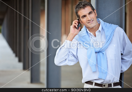 Casual smart man talking on the phone stock photo, Casual smart man talking on the phone and looking away by Tyler Olson