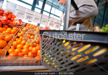Man in Supermarket stock photo, Closeup of a man carrying basket while buying fruits in the supermarket by Tyler Olson