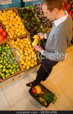 Buying Lemons stock photo, A male in a grocery store buying lemons - sharp focus on lemons by Tyler Olson
