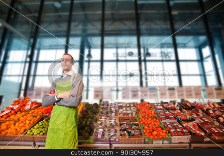 Grocery Store Owner Portrait stock photo, Portrait of a grocery store clkerk or owner in front of a vegetable counter by Tyler Olson