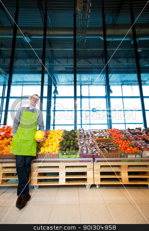 Grocery Store stock photo, An owner of a grocery store standing by fruits and vegetables by Tyler Olson