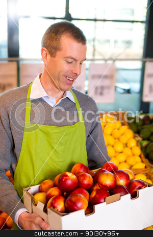 Grocery Store Peaches stock photo, A happy male grocer with a box of ripe peaches by Tyler Olson