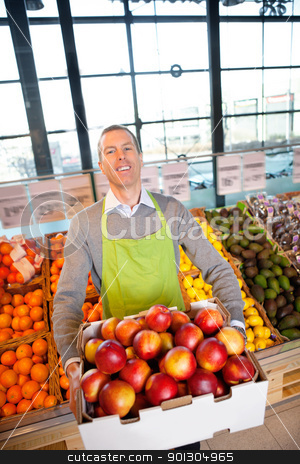 Supermarket Owner with Fresh Produce stock photo, Happy store owner with box of apples, looking at the camera by Tyler Olson