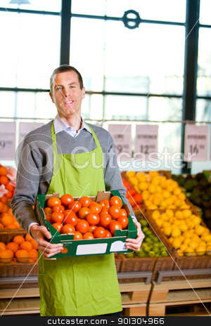 Grocery Store Owner stock photo, A friendly grocery store owner with a box of ripe tomatoes by Tyler Olson