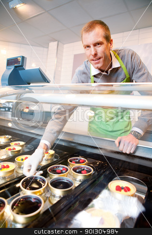 Fancy Desert Counter stock photo, A store clerk selling fancy deserts from a glass counter by Tyler Olson