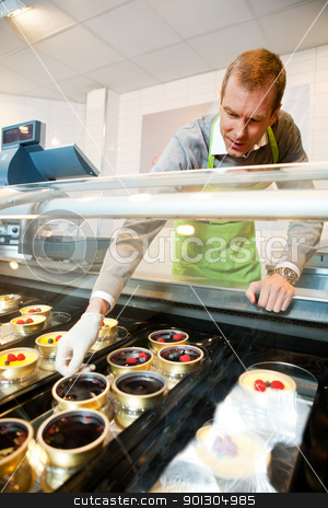 Gourmet Desert stock photo, A man selling gourmet deserts from behind a glass counter by Tyler Olson