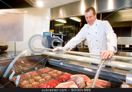 Fresh Meat Counter stock photo, A butcher at a fresh meat counter in a grocery store by Tyler Olson