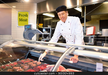 Fresh Meat Counter with Butcher stock photo, Butcher at a fresh meat counter helping customers by Tyler Olson