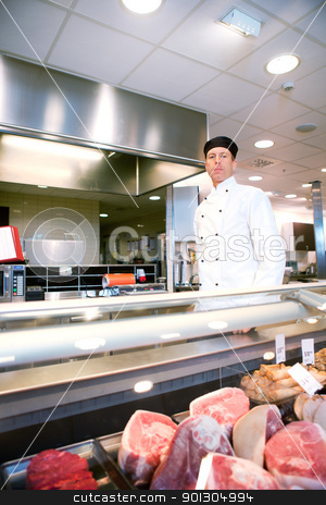 Butcher stock photo, A serious satisfied butcher behind a fresh meat counter in a deli by Tyler Olson