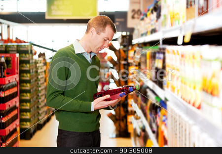 Male Shopping Comparing Products stock photo, A male shopper in a grocery store comparing products by Tyler Olson
