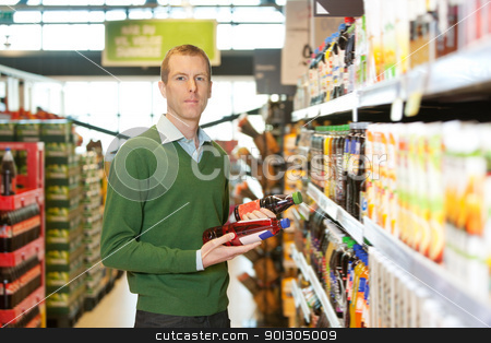 Product Comparison stock photo, Portrait of a man comparing two products in a grocery store by Tyler Olson