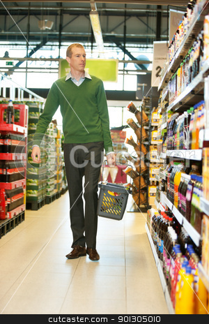 Man walking in grocery store stock photo, Mid adult man with shopping basket walking in grocery store and looking at products by Tyler Olson
