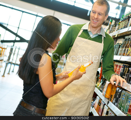 Helpful Grocery Store Clerk stock photo, Woman standing with smiling store worker while holding drink bottle in grocery store by Tyler Olson