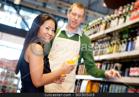 Grocery Store Help stock photo, An asian woman in a grocery store receiving help from a store clerk by Tyler Olson