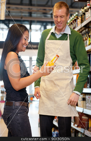 Grocery Store stock photo, A woman receiving help from a grocery store clerk - critical focus on woman by Tyler Olson