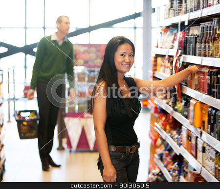 Portrait of a woman with man in background in store stock photo, Smiling woman looking at camera with man in the background in shopping store by Tyler Olson