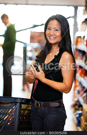Asian Woman with Cell Phone stock photo, Smiling woman looking at camera while holding mobile phone in hand with man in the background by Tyler Olson