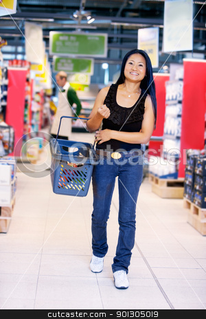 Asian Woman in Grocery Store stock photo, Smiling asian woman walking in grocery store carrying a shopping basket with store worker in the background by Tyler Olson