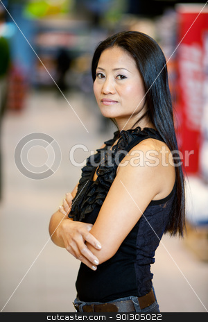 Asian Woman Standing in Supermarket stock photo, Asian woman standing in a supermarket looking at the camera by Tyler Olson