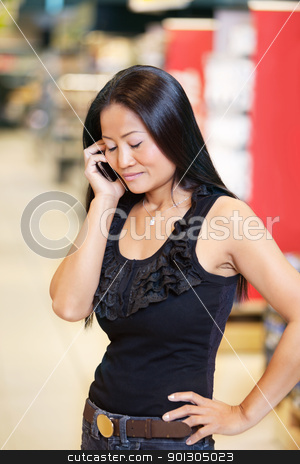 Woman smiling and talking on mobile phone stock photo, Smiling woman with eyes closed having conversation on mobile phone in shopping centre by Tyler Olson