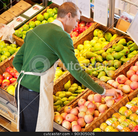 Man Working in Grocery Store stock photo, High angle view of store worker working in a grocery store by Tyler Olson
