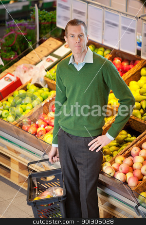 Portrait of serious man in shopping centre stock photo, Serious man with hand on hip looking at camera while shopping in a fruit store by Tyler Olson