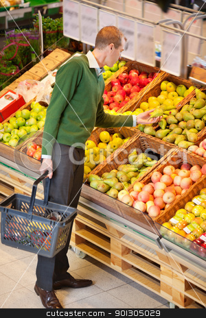 Man Buying Fruit stock photo, Adult man examining fruits to buy in shopping centre by Tyler Olson