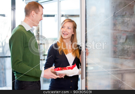 Couple Buying Groceries stock photo, A happy couple choosing groceries from the frozen food section in a supermarket by Tyler Olson