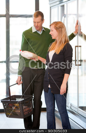 Supermarket Couple stock photo, A happy couple buying frozen food in a supermarket by Tyler Olson