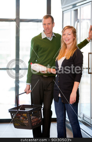 Happy couple in Supermarket stock photo, A happy caucasian couple buying grocers in a supermarket frozen section by Tyler Olson